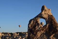 Balões de ar quente atrás da rocha com céu claro Imagens de Stock Royalty Free