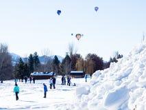 Balões de ar quente coloridos que voam acima de um campo coberto de neve Fotos de Stock