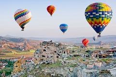 Balões de ar quente coloridos que voam sobre Cavusin em Cappadocia foto de stock royalty free