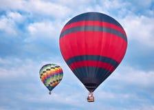 Balões de ar quente em voo Dois balões coloridos que voam no céu azul nebuloso Fotos de Stock Royalty Free