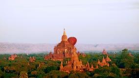Balões de ar quente que voam no nascer do sol sobre templos budistas antigos em Bagan myanmar filme