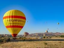 Balões de ar quente que voam sobre e que aterram no Cappadocia Imagem de Stock