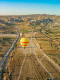 Balões de ar quente que voam sobre e que aterram no Cappadocia Imagem de Stock Royalty Free