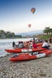 Balões de ar quente que voam sobre Nam Song River e caiaque do turista em Vang Vieng, estância turística popular no Lao PDR Fotos de Stock