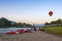 Balões de ar quente que voam sobre Nam Song River e caiaque do turista em Vang Vieng, estância turística popular no Lao PDR Foto de Stock