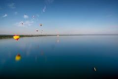 Balões de ar quente que voam sobre o lago Fotografia de Stock Royalty Free