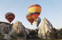 Balões de ar quente sobre o terreno de Cappodocia Fotos de Stock Royalty Free