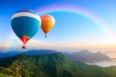 Balões de ar quentes coloridos que voam sobre a montanha Fotografia de Stock
