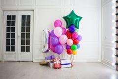 Balões de cores diferentes com os presentes para o feriado em uma sala Fotografia de Stock Royalty Free