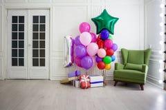 Balões de cores diferentes com os presentes para o feriado em uma sala Imagens de Stock Royalty Free