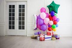 Balões de cores diferentes com os presentes para o feriado em uma sala Imagens de Stock