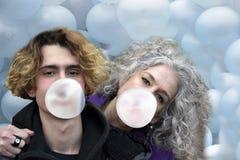 Balões de sopro da mãe e do filho com pastilha elástica imagem de stock