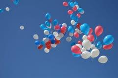 Balões de voo bonitos sobre o céu azul foto de stock