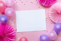 Balões e confetes coloridos na tabela cor-de-rosa com Livro Branco no centro para o texto imagens de stock