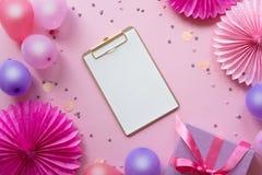 Balões e confetes coloridos na tabela cor-de-rosa com Livro Branco no centro para o texto Fundo do anivers?rio, do feriado ou do  fotografia de stock