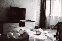 Balões no assoalho da sala e nos pés de uma menina que senta-se no sofá imagens de stock royalty free