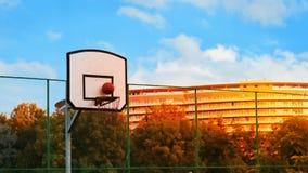 Bal in basketbalhoepel met blauwe hemel bij zonsondergang royalty-vrije stock afbeeldingen