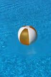 Bal die in blauw water drijft Stock Foto's