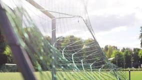 Bal die in voetbaldoel netto vliegen op gebied stock videobeelden