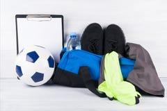 Bal en blauwe zak met sportendingen voor een voetbal opleiding op een lichte achtergrond stock afbeelding