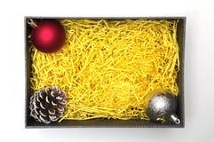 Bal en denneappel in zwarte giftdoos met gele verpakking mater Royalty-vrije Stock Afbeelding