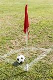 Bal en Rode vlag in hoek van voetbalgebied Stock Foto's
