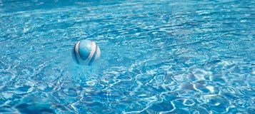 Bal om in de pool in duidelijk blauw water te spelen stock foto's