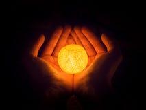 Bal van licht in handen Stock Foto