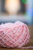 Bal van roze breiend garen met lint Stock Fotografie