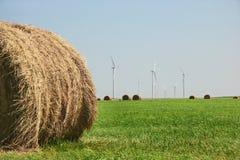Bala de feno e turbinas de vento imagens de stock