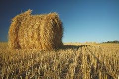 Bala de heno en campo con la paja y el cielo del trigo en la tierra de cultivo en s imagenes de archivo