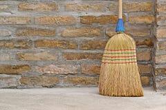 Balai de ménage pour le nettoyage de plancher se penchant sur le mur de briques photo libre de droits