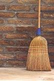 Balai de ménage pour le nettoyage de plancher se penchant sur le mur de briques photo stock