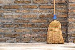 Balai de ménage pour le nettoyage de plancher se penchant sur le mur de briques image stock