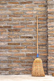 Balai de ménage pour le nettoyage de plancher se penchant sur le mur de briques photographie stock
