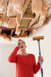 Balai de participation de femme sous le plafond endommagé Images stock