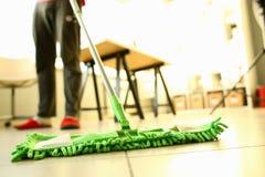 Balai en plastique vert nettoyant le plancher sale léger stratifié photographie stock