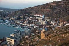 Balaklava fjärd, Crimea Panoramautsikt från kullen med fästningcembaloen till lilla staden med hamnen och yachter med fartyg arkivbilder