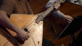 Balalaika ξύλινο στα χέρια του μουσικού Λαϊκή μουσική τέχνη αγροτικού του παραδοσιακού Το άτομο παίζει το Balalaika απόθεμα βίντεο