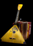 Balalaika and accordion. On a black background the photo a light brush Royalty Free Stock Photography