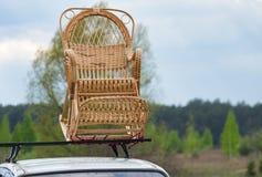Balançar-cadeira de vime em um telhado de um automóvel de passageiros fotos de stock royalty free