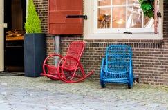 Balançar-cadeira vermelha e azul da rua na entrada à loja doce foto de stock
