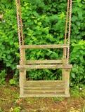 Balanço abandonado do bebê no canto do jardim de infância Arbustos verdes frescos no fundo Fotos de Stock
