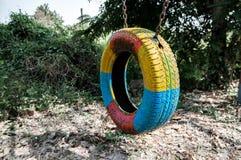 Balanço abandonado feito do pneu velho pintado Imagens de Stock