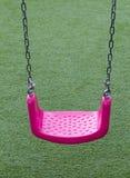 Balanço cor-de-rosa em gramas verdes Fotos de Stock Royalty Free
