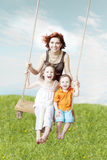 Balanço da família de encontro ao céu e à grama Fotos de Stock