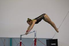 Balanço das barras paralelas da menina da ginasta Fotografia de Stock