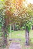 Balanço de madeira no vintage do jardim imagem de stock