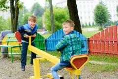 Balanço engraçado dos meninos em uma balanço-placa amarela imagem de stock