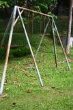 Balançoir rouillée à un stationnement vide de la pièce d'enfants Photos stock